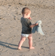 Boy on beach holding small soft toy while sucking thumb